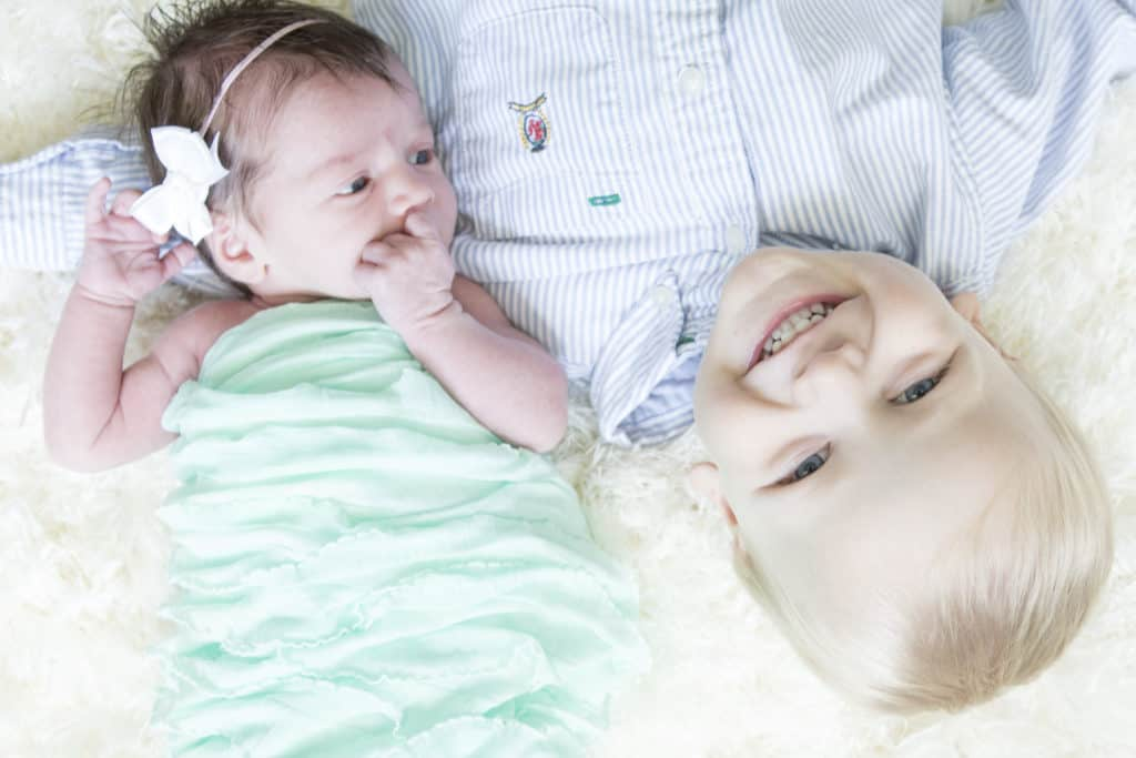 A toddler boy and a newborn girl adorably laying on a rug upside down to each other